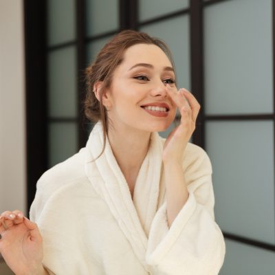 Cheerful lovely young woman in bathrobe standing and touching her face in bathroom